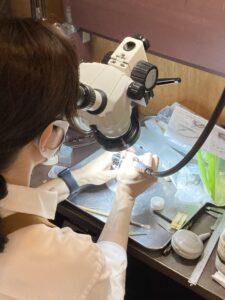 彫金教室で実体顕微鏡を使いダイヤを石留めする写真